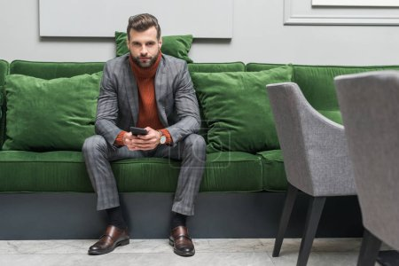 Photo for Handsome man in formal wear sitting on green sofa, looking at camera and using smartphone - Royalty Free Image