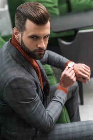 Photo pour Homme en vêtements assis sur le canapé vert et réglage montre sur place - image libre de droit
