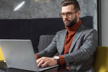 Photo pour Bel homme d'affaires dans les vêtements et lunettes assis à table et en tapant sur l'ordinateur portable au restaurant - image libre de droit