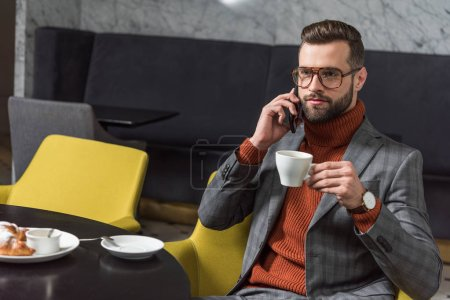 serious handsome man in formal wear talking on smartphone while drinking coffee in restaurant