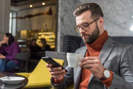 Photo for Focused handsome man in formal wear and glasses using smartphone while drinking coffee in restaurant - Royalty Free Image