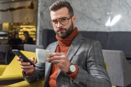 Photo for Handsome man in formal wear looking at camera, using smartphone and drinking coffee in restaurant - Royalty Free Image