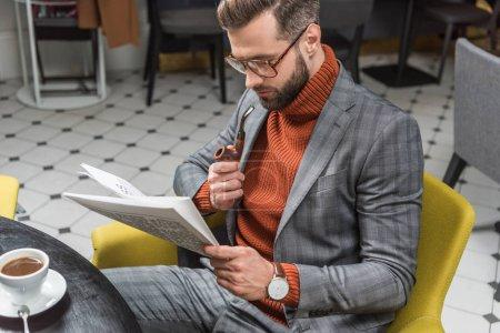 Photo pour Homme élégant en vêtements assis à table, lisant le journal et pipe de tabagisme en restaurant - image libre de droit