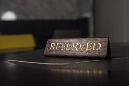 selective focus of reserved sign on black table in cafe