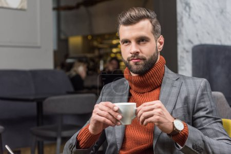 Photo for Handsome bearded man in formal wear drinking coffee in restaurant - Royalty Free Image