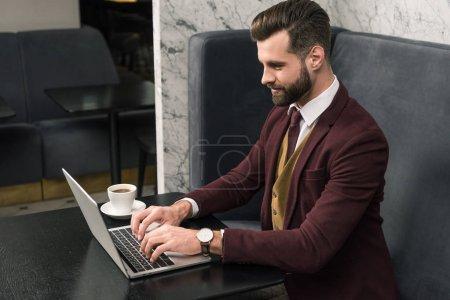 Photo pour Bel homme d'affaires assis à table avec une tasse de café et tapant sur ordinateur portable dans le restaurant - image libre de droit