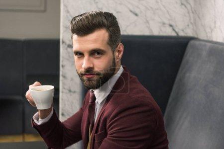 schöner Geschäftsmann in formeller Kleidung, der in die Kamera blickt, am Tisch sitzt und im Restaurant Kaffee trinkt