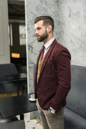confident businessman in formal wear with hand in pocket looking away