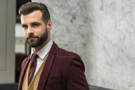 portrait of handsome businessman in formal wear looking away