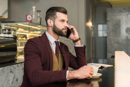 serio hombre de negocios guapo en ropa formal sentado en la mesa y hablando en el teléfono inteligente en el restaurante