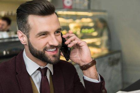 handsome smiling businessman in formal wear talking on smartphone