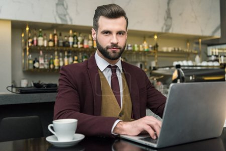 Photo for Handsome businessman looking at camera, sitting at table with cup of coffee and typing on laptop in restaurant - Royalty Free Image