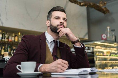 Photo pour Homme d'affaires réfléchi en tenue de cérémonie assis et écrivant dans un carnet à table dans un restaurant - image libre de droit