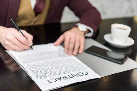 vue recadrée d'un homme d'affaires en tenue de cérémonie assis à table et signant un contrat
