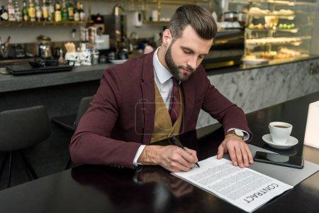 Photo pour Bel homme d'affaires en tenues assis à table et la signature du contrat - image libre de droit
