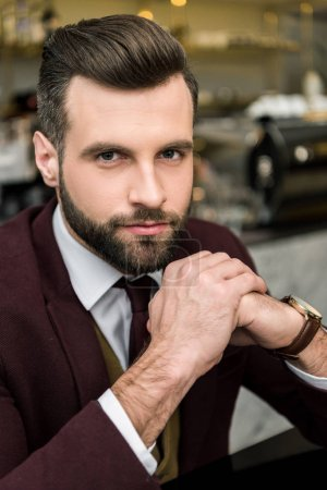 portrait of handsome businessman in formal wear with folded hands looking at camera