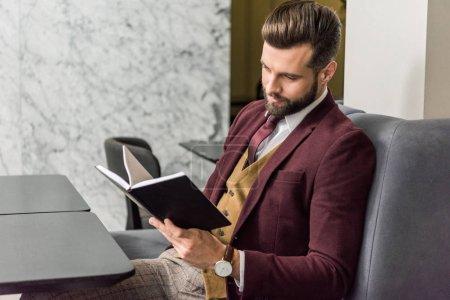 Photo pour Bel homme d'affaires en tenue formelle assis au restaurant et regardant carnet - image libre de droit