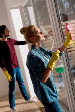 couple in rubber gloves cleaning window in apartment