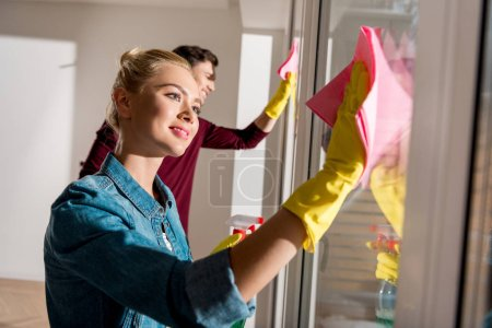 Photo for Beautiful girl in rubber gloves cleaning window with husband at background in apartment - Royalty Free Image