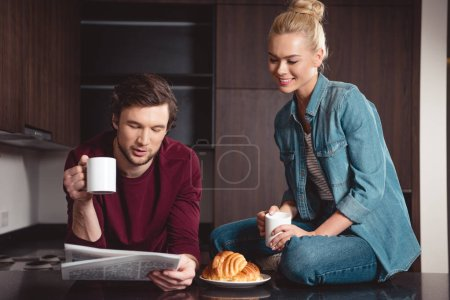 handsome man holding coffee cup and reading newspaper while attractive girl sitting on table and smiling in kitchen