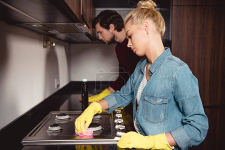 beautiful girl and handsome man in rubber gloves cleaning kitchen at home