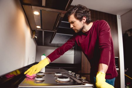 Photo for Serious man in rubber gloves cleaning kitchen - Royalty Free Image