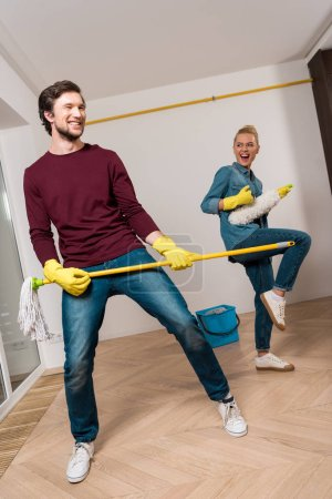 Photo for Cheerful family couple in rubber gloves performing with cleaning equipment at home - Royalty Free Image