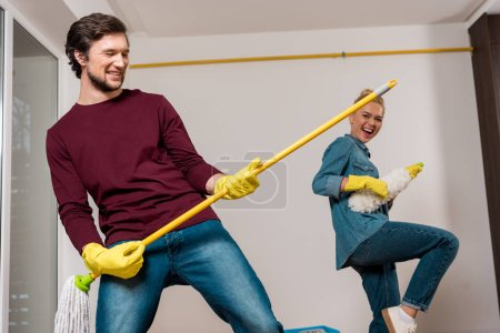 cheerful man performing with mop and attractive girl holding duster at background