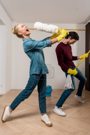Photo for Happy girl in rubber gloves singing with duster while husband performing with mop in apartment - Royalty Free Image