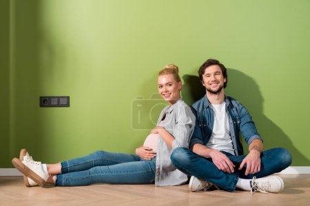Photo for Pregnant girl touching belly with both hands, looking at camera and sitting on floor with handsome man - Royalty Free Image
