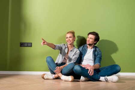 handsome man sitting on floor with attractive girl pointing with finger in apartment