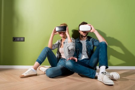 surprised girl and man sitting on floor and holding virtual reality headsets on heads