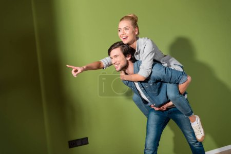 handsome man giving piggyback ride to beautiful wife pointing with finger in apartment