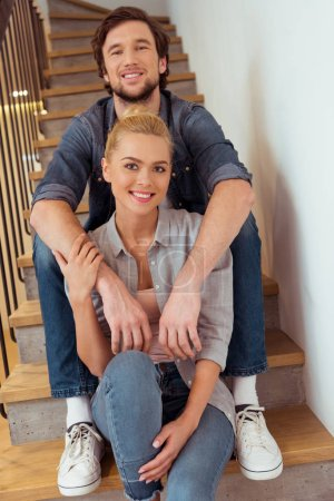 smiling man sitting on stairs and holding hands on shoulders of beautiful wife