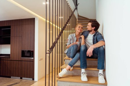 loving couple sitting on stairs and looking at each other