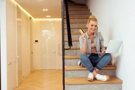 Photo pour Jeune fille souriante avec carte de crédit et l'ordinateur portable assis dans les escaliers et en regardant la caméra - image libre de droit