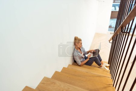 Photo for Attractive girl sitting on stairs and typing on laptop keyboard - Royalty Free Image