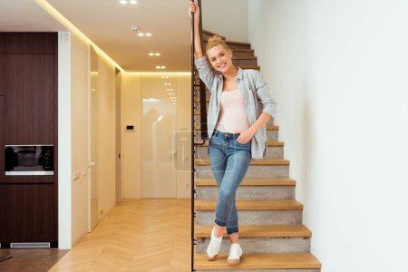 Photo pour Jolie jeune fille debout sur des marches et regardant la caméra à la maison - image libre de droit