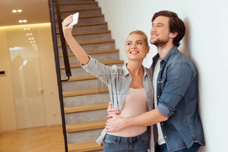 Photo for Cheerful family couple taking selfie near stairs at home - Royalty Free Image