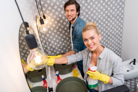 Photo for Handsome man and attractive girl in rubber gloves girl cleaning mirrors and looking at camera in bathroom - Royalty Free Image