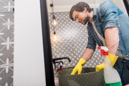 mirror reflection of handsome man in rubber gloves cleaning sink in bathroom