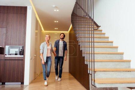 Photo pour Joyeux couple main dans la main près des escaliers à la maison - image libre de droit