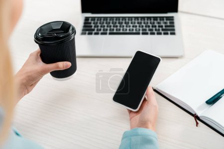 partial view of businesswoman with coffee to go and smartphone with blank screen at workplace