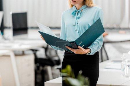 Photo pour Vue partielle de la femme d'affaires avec le dossier au bureau - image libre de droit