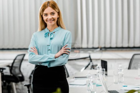Photo for Portrait of smiling businesswoman in formal wear with arms crossed in office - Royalty Free Image