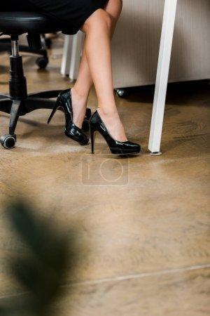 Photo pour Vue partielle de la femme d'affaires en chaussures noires sur le lieu de travail au bureau - image libre de droit