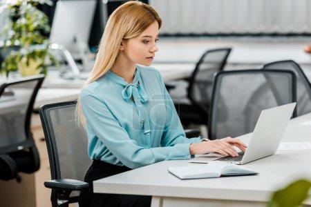Photo pour Vue latérale d'une jeune femme d'affaires travaillant sur ordinateur portable au lieu de travail avec ordinateur portable au bureau - image libre de droit