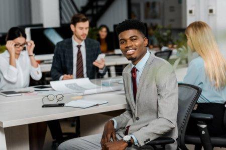 Photo pour Mise au point sélective du sourire, homme d'affaires américain africain et collègues de travail au lieu de travail au bureau - image libre de droit