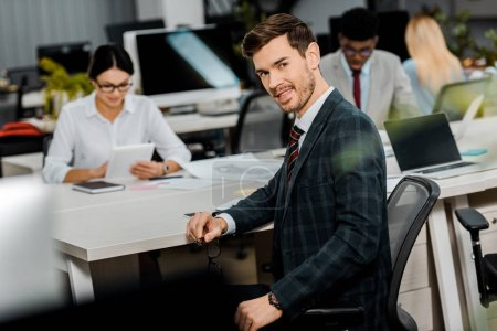 Photo for Selective focus of young businessman in suit and multiracial colleagues in office - Royalty Free Image