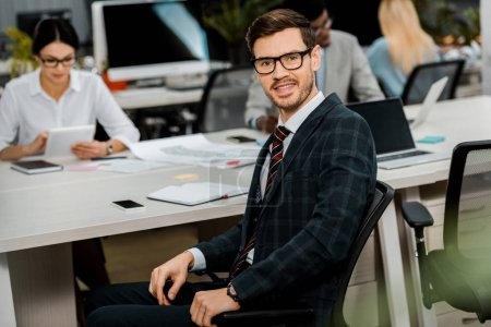 Photo for Selective focus of young businessman in suit and eyeglasses and multiracial colleagues in office - Royalty Free Image